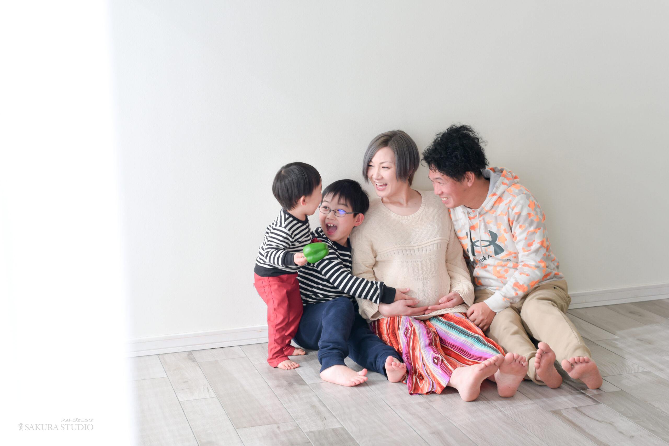 マタニティ 家族写真 1歳の子供に3人が話しかけている