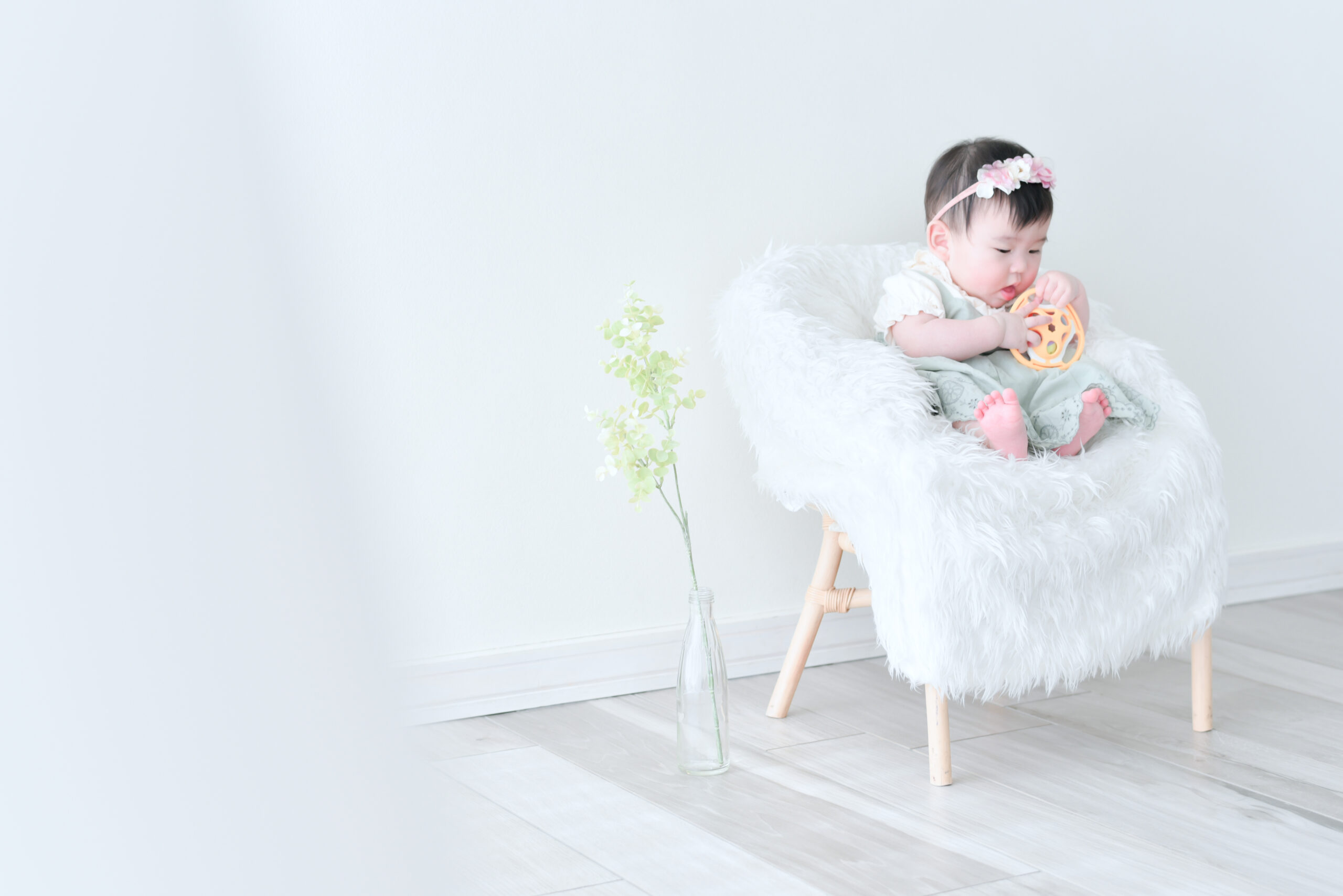 生後6ヶ月 赤ちゃん 女の子 自分のおもちゃをにぎにぎ 時々あむあむ味見 おもちゃに夢中になって丸まっている体のフォルムが可愛い フォトスタジオで撮影 宇都宮写真館 フォトジェニックサクラスタジオ