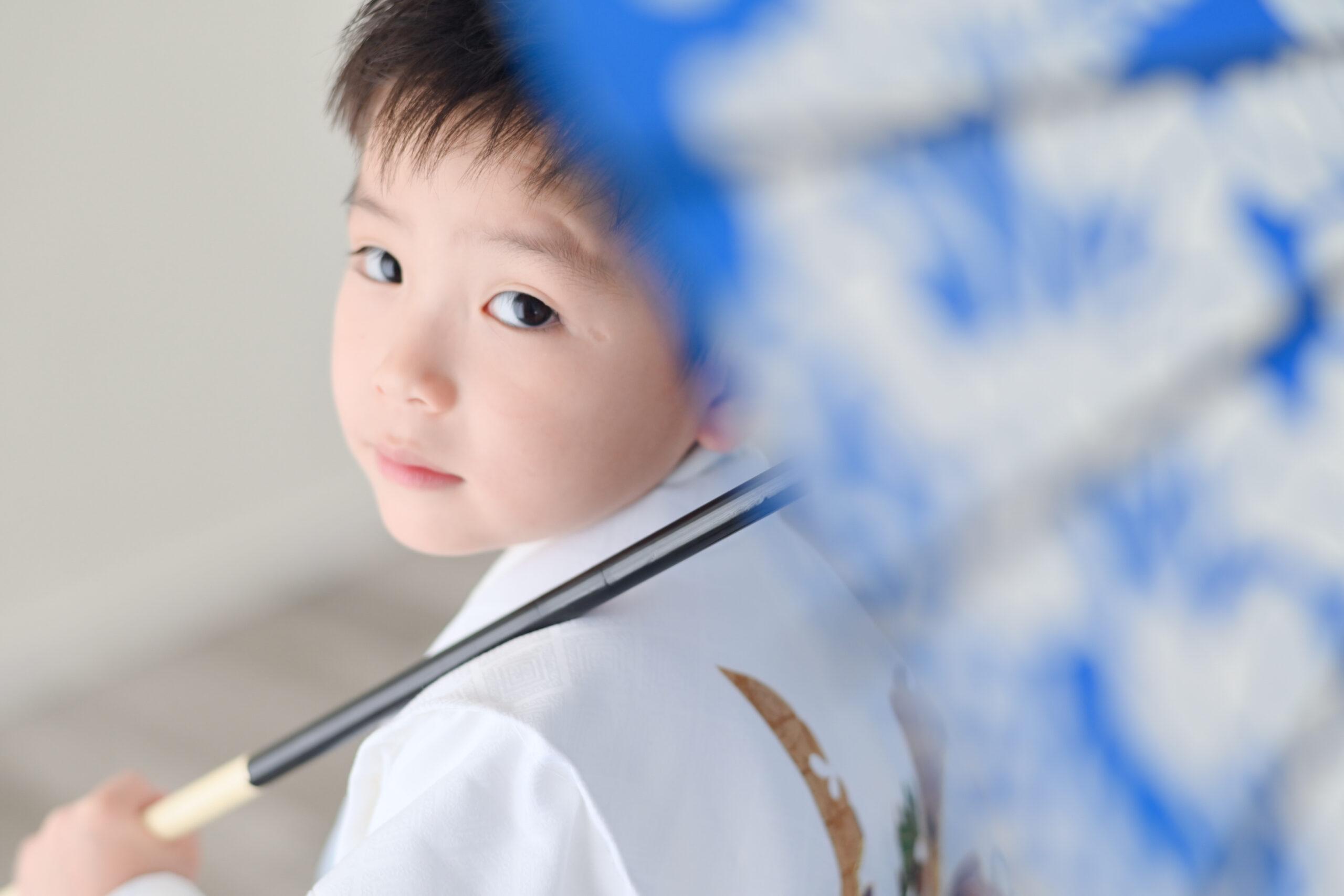 七五三撮影5歳の男の子が番傘越しに振り返り